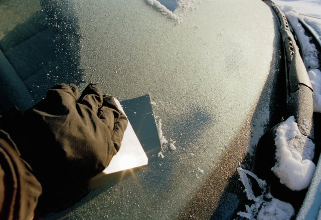 Person scraping frost off a car windshield