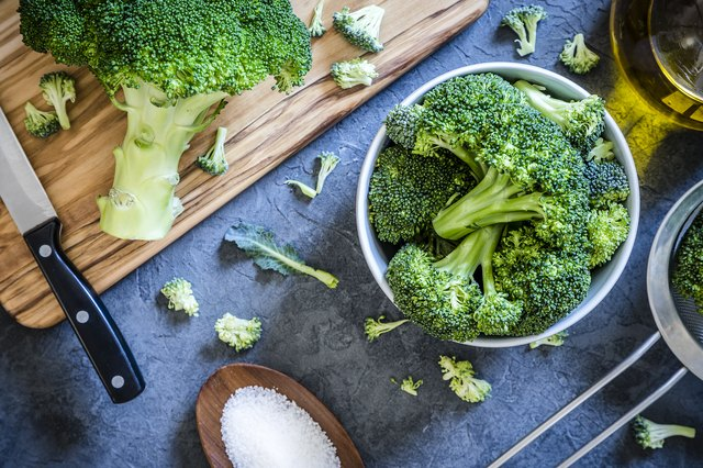 Cutting and cooking broccoli on grey textured backdrop