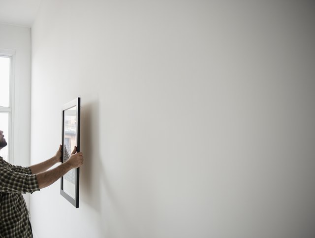 USA, New Jersey, Jersey City, Side view of man hanging picture on wall