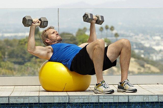 Man doing stability ball bench press exercise for better sex
