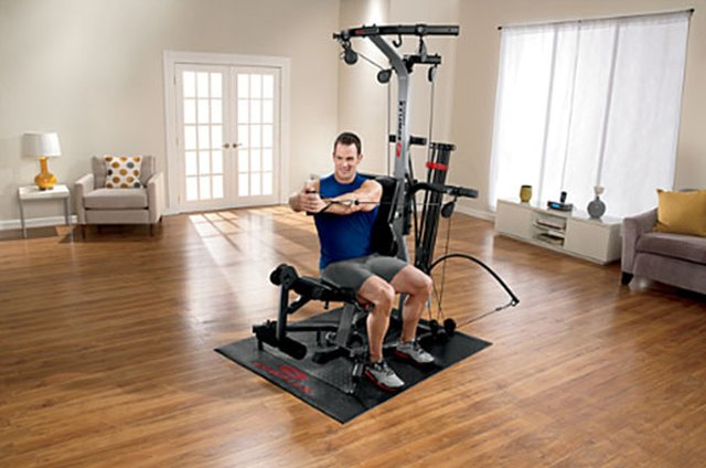Portrait of man using exercise equipment in gymnasium