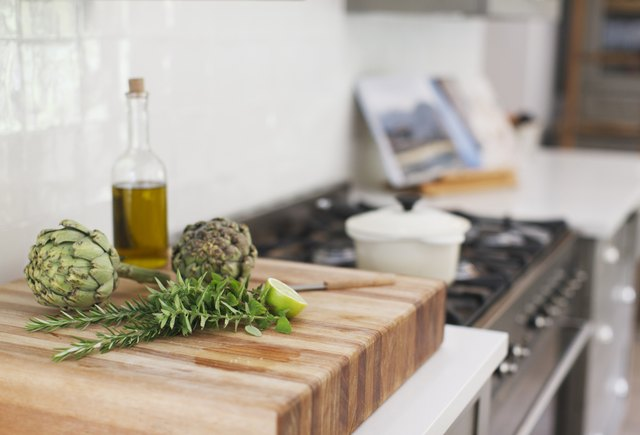 Artichokes, rosemary, olive oil and lime on a cutting board
