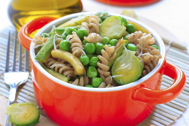 Wholegrain pasta with green vegetables in ceramic pan