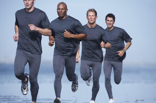 Four men jogging on beach