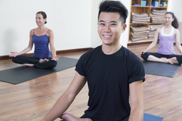 Smiling man sitting cross-legged in a yoga class