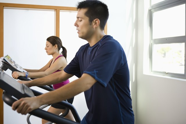 Young couple working out on elliptical machines in gym