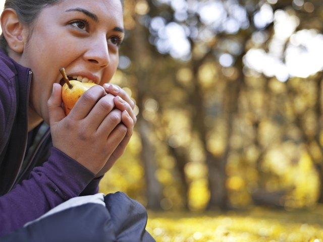 Woman eating pear, close-up