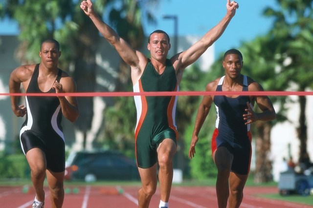 portrait of a young male athlete crossing the finish line first with his arms raised up in victory