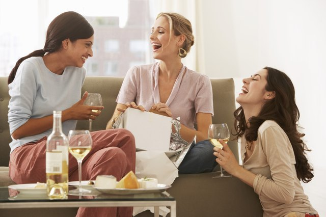 Three young women gathered on sofa, drinking wine and laughing