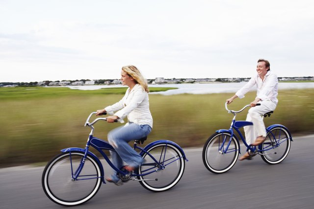 Couple riding bikes by marshland