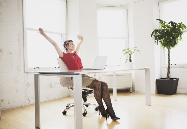 Excited young adult woman working in office