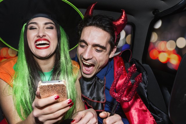 Halloween witch and devil laughing in back of car