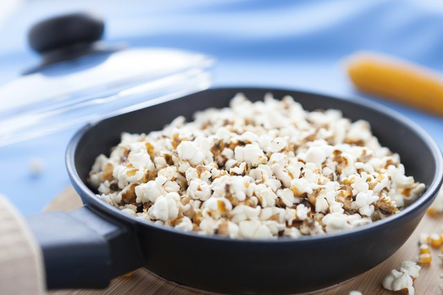 Raw corn and popcorn in a frying pan