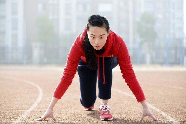 Athletic Asian woman in start position on track