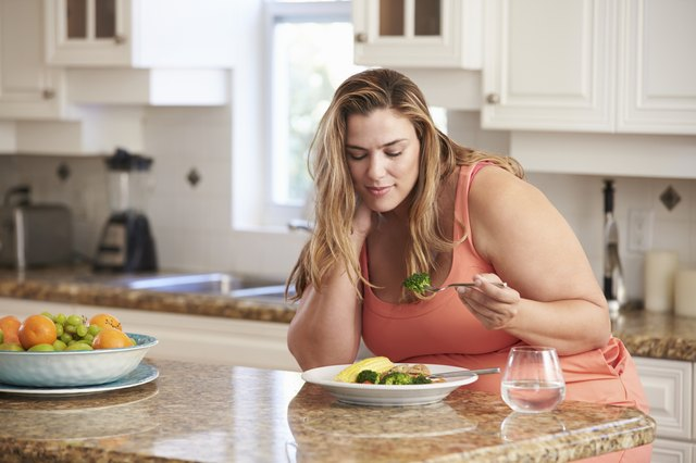 Overweight Woman Eating Healthy Meal In Kitchen