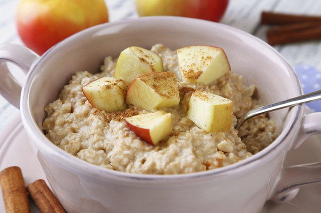 A bowl of oatmeal with apples and cinnamon on a wooden table