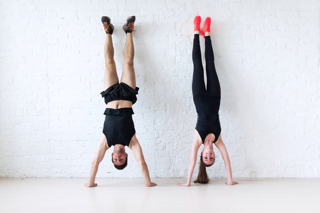 sportsmen woman and man doing a handstand against wall concept