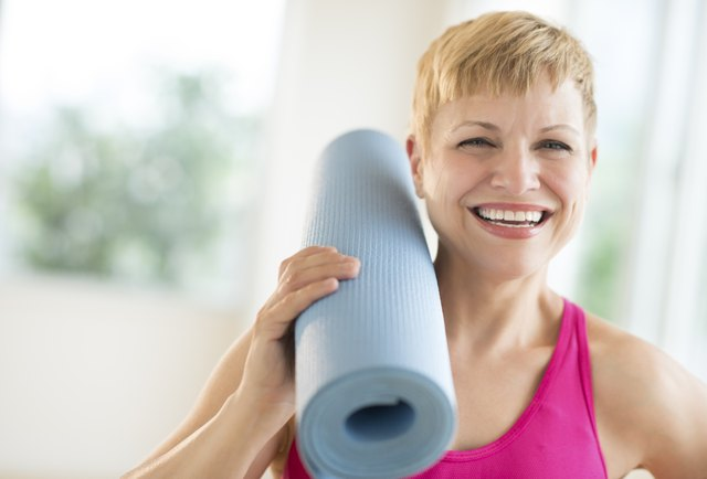 Cheerful Woman Holding Rolled Up Exercise Mat