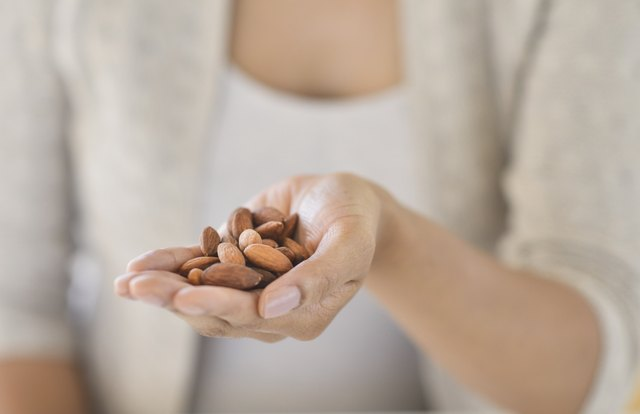 USA, New Jersey, Jersey City, Close-up of woman holding almonds