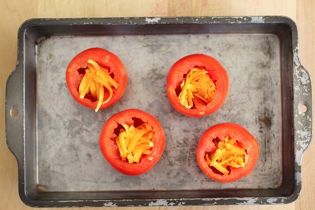 Add grated cheese to the bottom of the hollowed-out tomatoes.