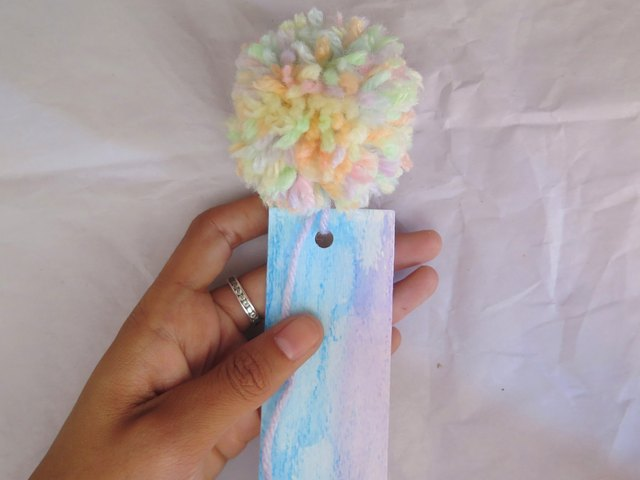 Looping the yarn pompom tail through the hole punch.