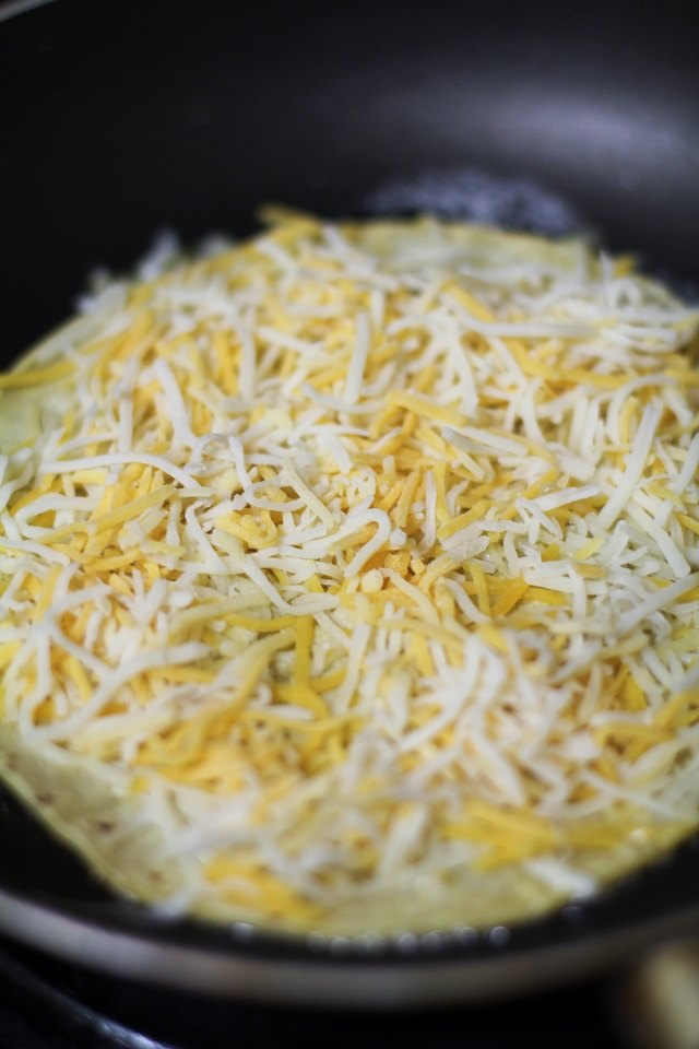 Top your tortilla with grated cheese.