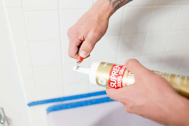 Use a utility knife to slice an angled chunk off the end of your caulk tube.