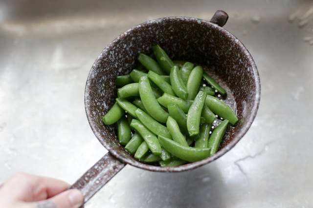 Drain the peas from the water. Pick out any peas or pea pods that have dark spots on them or otherwise appear damaged, and discard them.