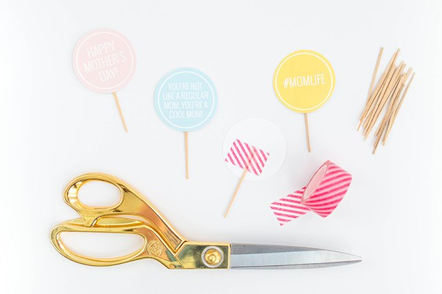 Attach toothpicks to the backs of the printed mini cupcake toppers using tape.