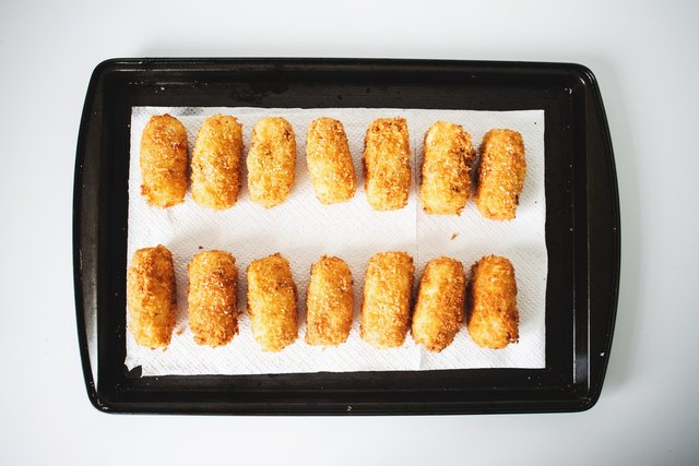 Put the cooked tots on a baking tray to drain off extra oil.