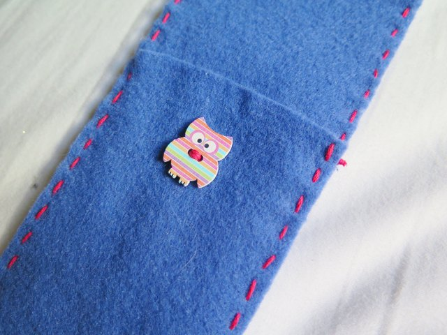 The owl button sewn onto the case.