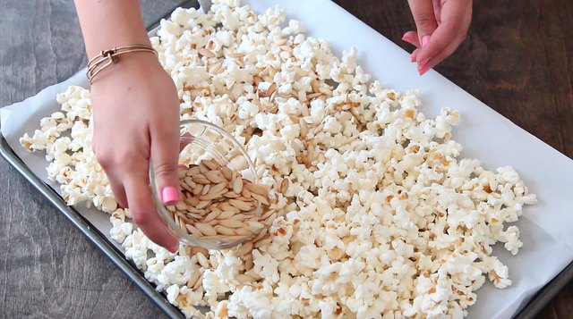 Place popcorn and pumpkin seeds on cookie sheet.
