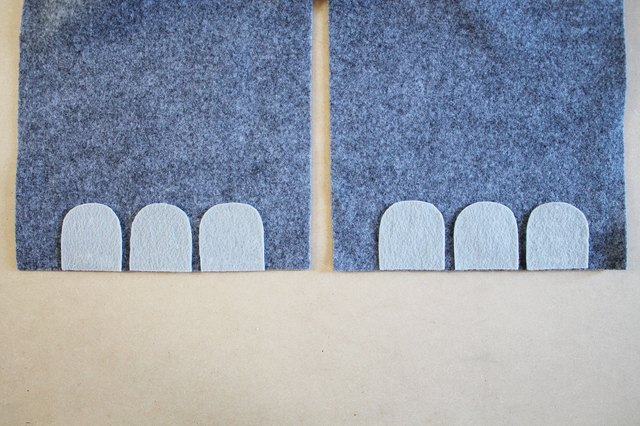 Center the toenails at the bottom edge of the jumpsuit leg's hem.