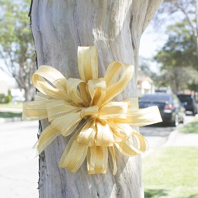 A bold, beautiful yellow bow looks right at home on a tree.