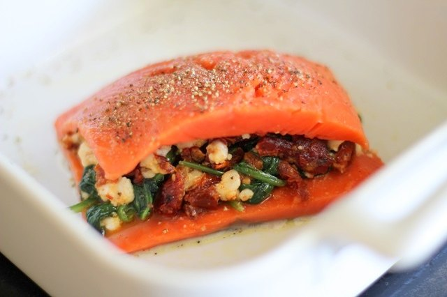 Put the raw stuffed salmon in the baking dish.