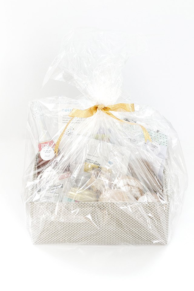 Wrap the gift basket with clear cellophane and finish with a bow.