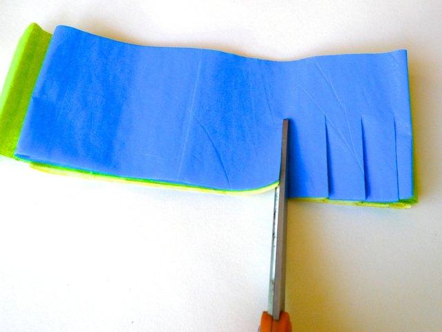 Frange à la longueur des bandes de tissu avec des ciseaux.