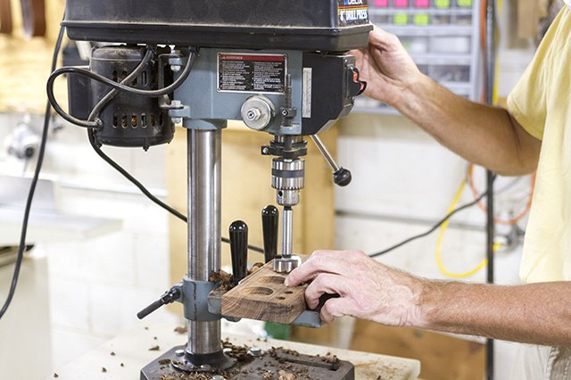 Drill out the four holes to later be used as supply wells with a drill press.