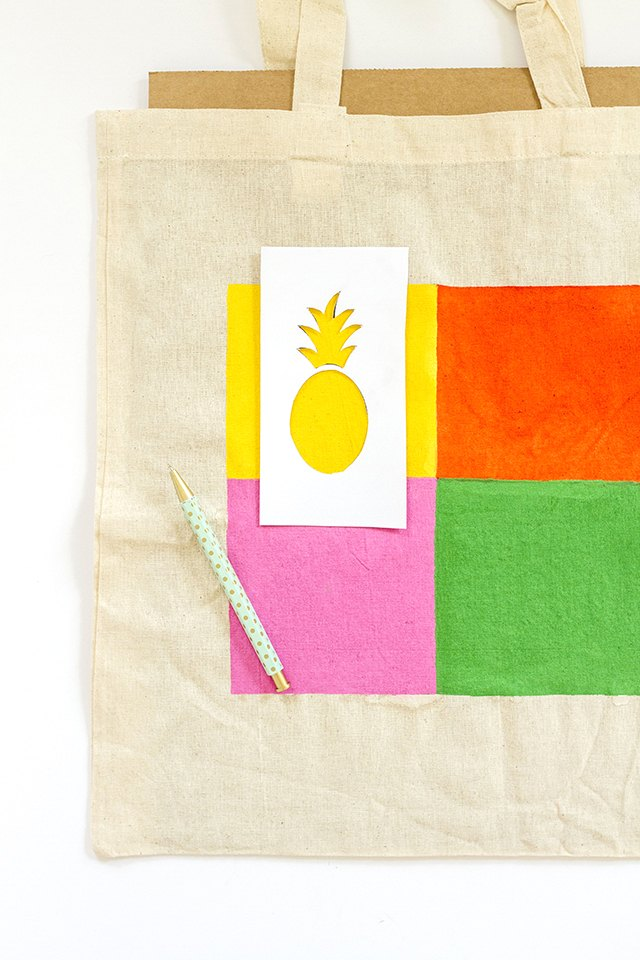 Lay down and trace the pineapple stencil on each square.