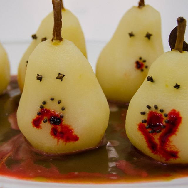 Poached pears with faces made of cloves
