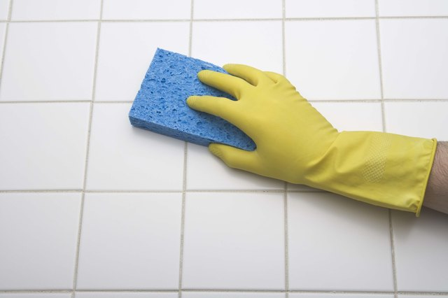 Person using sponge to clean tile