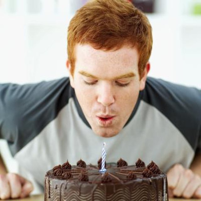 Man S Out Candle On Birthday Cake