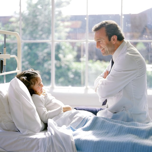 Doctor talking to female child in hospital bed.