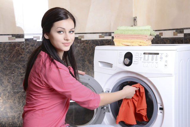 Woman putting clothes into a dryer.