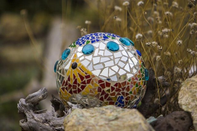 Create a quirky mosaic orb out of a bowling ball and broken tiles.
