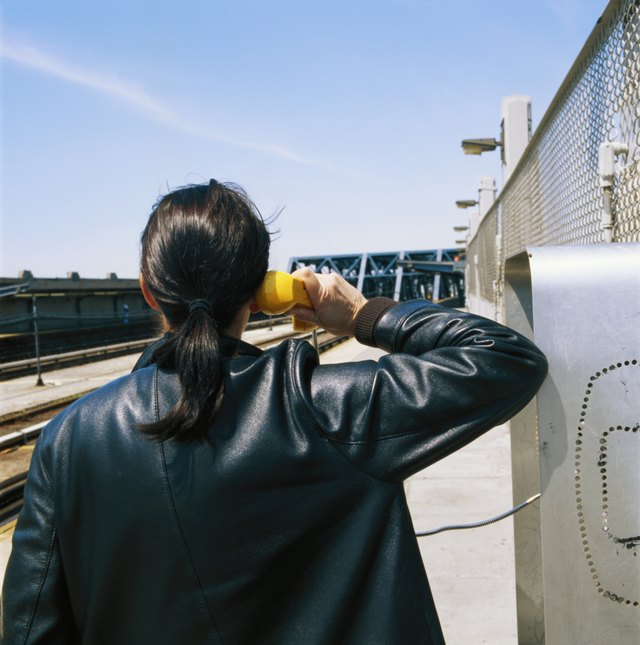 Man wearing leather jacket and using payphone.