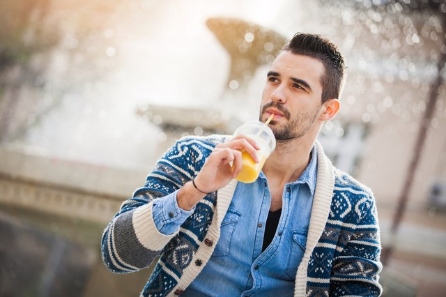 Young man drinking a yellow smoothie