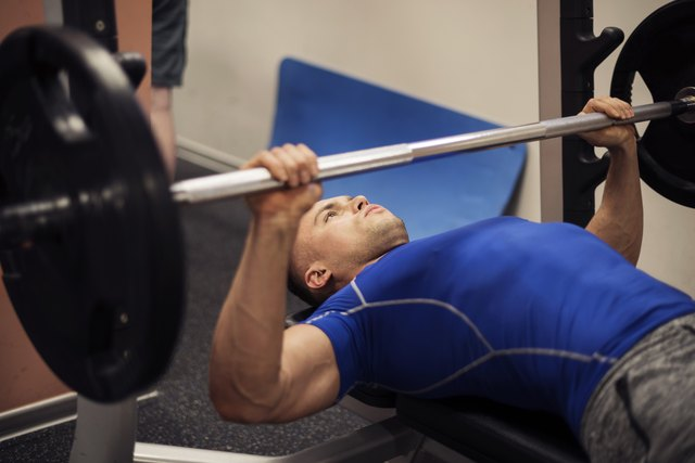 Focused man doing workout on weight bench