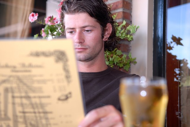 Man sitting at cafe reading menu