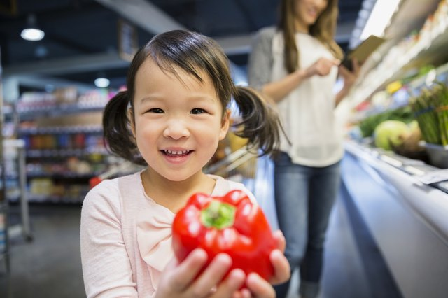 Portrait of smiling girl holding red bell pepper